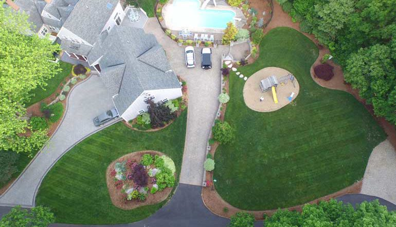 professionally maintained lawn and paver driveway overhead view